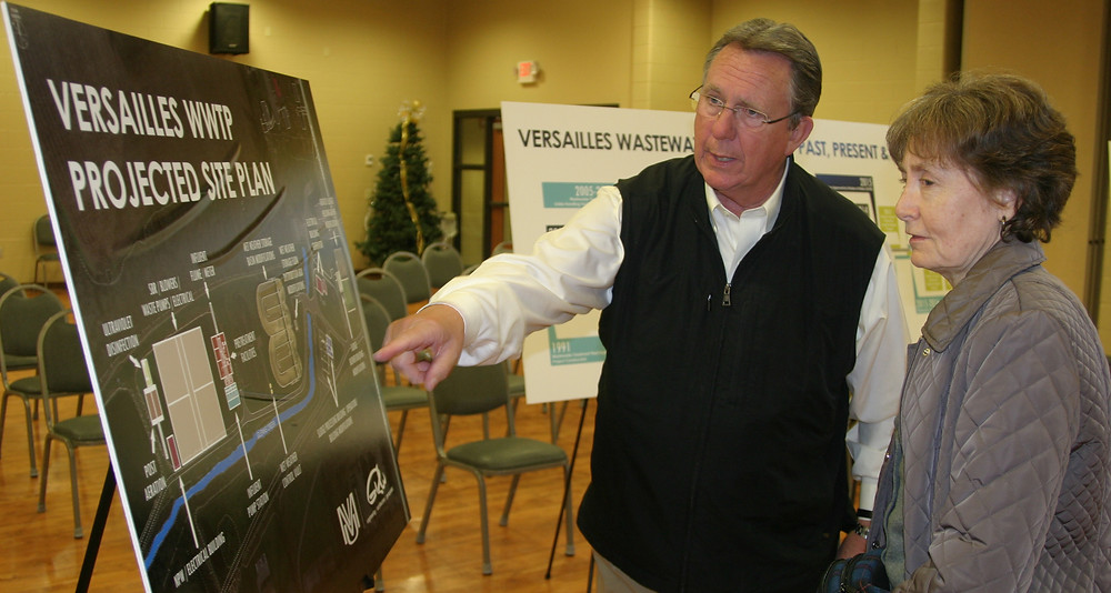KEN KERKHOFF was one of the Versailles City Council members who attended the Dec. 17 public meeting about the city's planned rate hikes needed to pay for a new $20 million wastewater treatment plant. He gave Evalee Gress a guided tour of the placards explaining the plan for the plant. (Photo by John McGary)