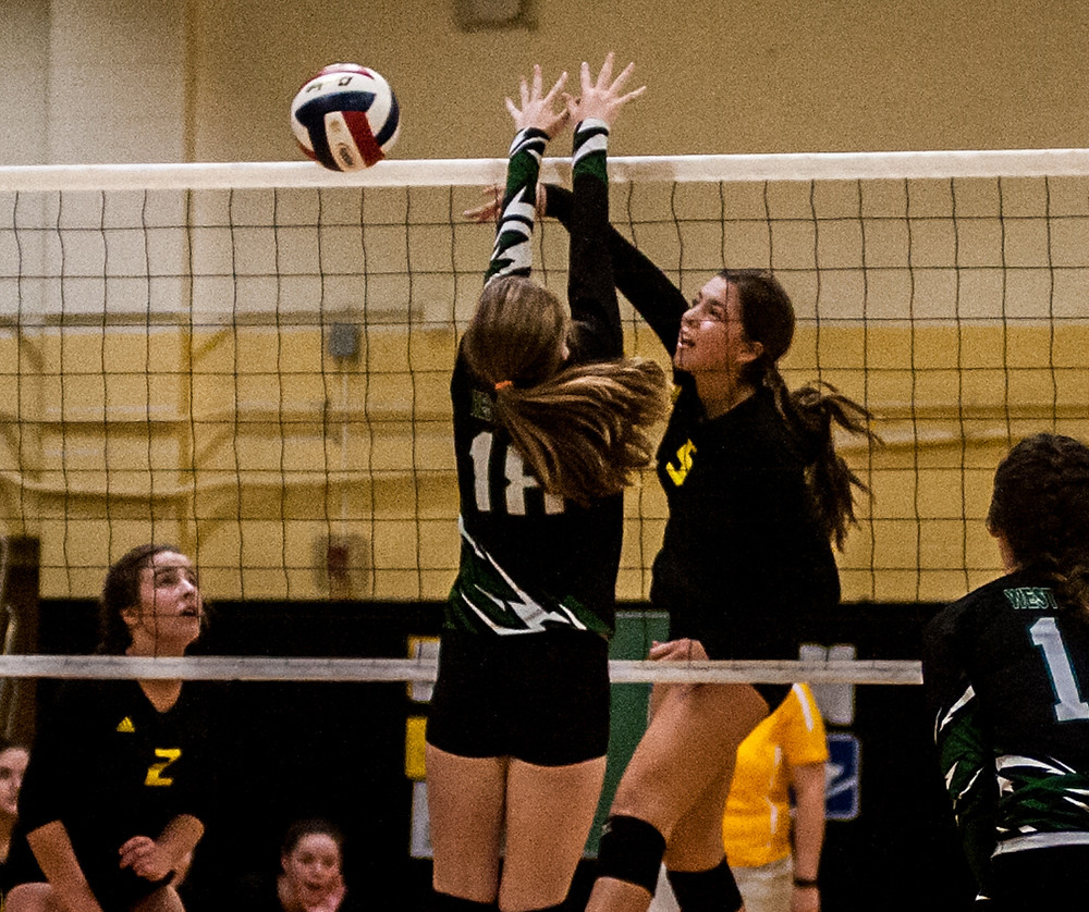 PIPER MCCOUN makes a kill in the fourth set against Western Hills. (Photo by Bill Caine)