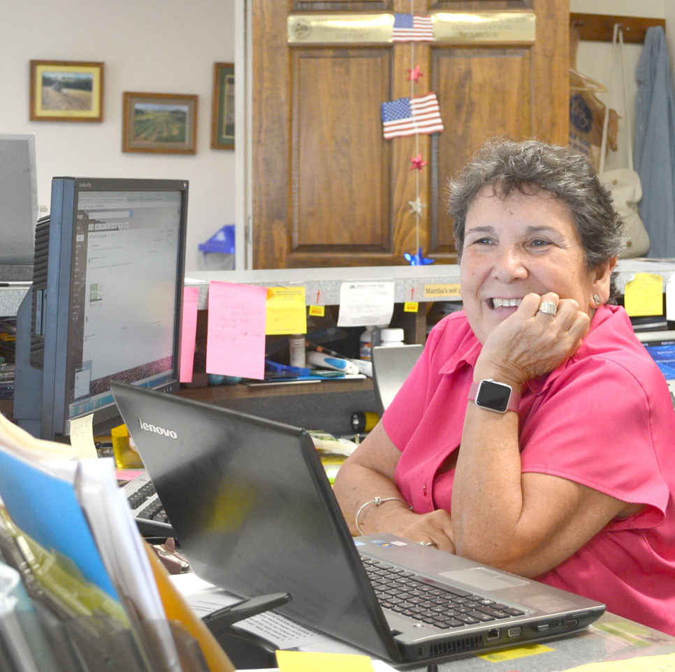 """MARTHA NEWBY will be honored for her many years of service to the Woodford County Conservation District and local farmers during a retirement reception this afternoon, July 28, from 4 to 6, in the Mackie Room of the Agricultural Resource Building. """"Everyone knows Martha and everyone likes Martha,"""" says farmer Donald Mitchell. (Photo by Bob Vlach)"""