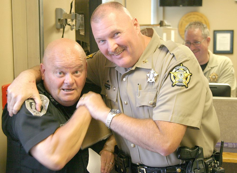 """WOODFORD SHERIFF Wayne """"Tiny"""" Wright, sporting a mustache just as he did the day he began his law enforcement career 32 years ago, puts long-time colleague Versailles Police Officer Jimmy Sewell in a friendly headlock in the county courthouse. Behind them, Deputy Joe Carter enjoys their antics. Of leaving the post he's held since December 2006, and a career that began when he was 21, Wright said, """"The job's more than just a badge and a gun. It's the community."""" (Photo by John McGary)"""