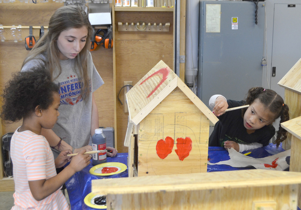 KASEY MONTGOMERY, a sophomore at Woodford County High School, provided guidance to Northside Elementary first-graders Hannah McColl, left, and Audia Rose when they applied paint to the exterior of a Little Free Library last Friday at WCHS. (Photo by Bob Vlach)