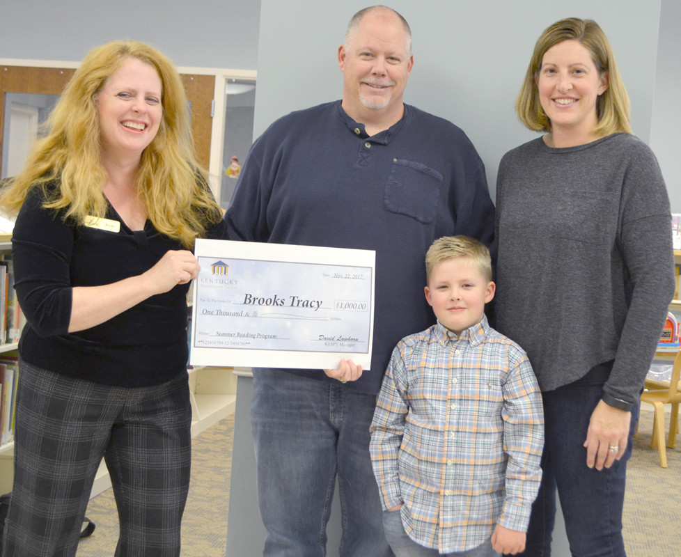 """BROOKS TRACY and his parents, Chris and Susan Tracy, are pictured with Becky Munoz, far left, youth services librarian at the Woodford County Library. Brooks and his family were awarded a $1,000 college savings account on Nov. 22 after he was named one of eight winners in a reading program: """"Read. Save for College. Change the World."""" (Photo by Bob Vlach)"""