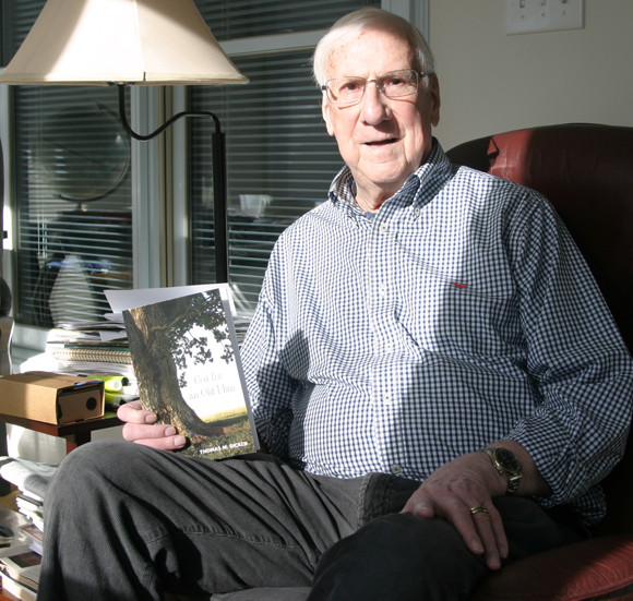 """THOMAS DICKEN, retired college professor and author, sits on his back porch with a copy of """"God for an Old Man,"""" a blend of autobiography and philosophy developed over a lifetime. (Photo by John McGary)"""
