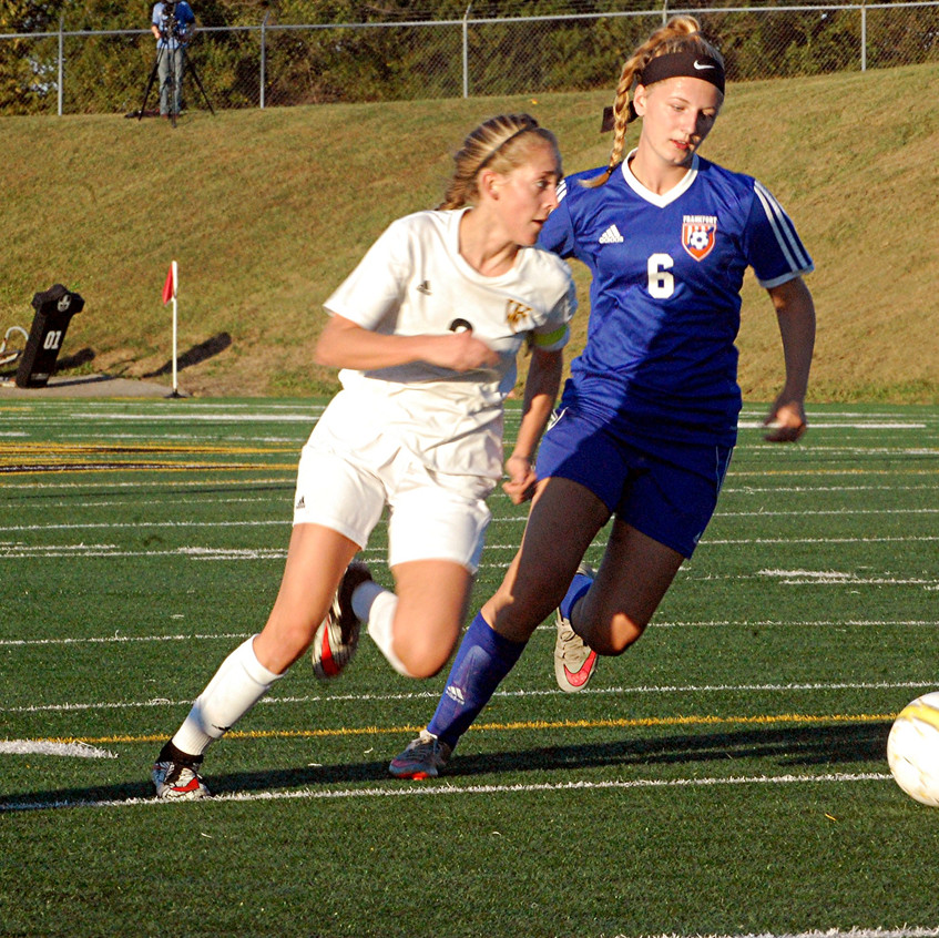 CAITLYN BURDINE drives toward the ball while looking for a teammate to pass to during the Woodford County High School girls' soccer team's opening round game against Frankfort at home in Community Stadium on Monday, Oct. 10. The senior ended the night with seven goals and one assist as the Lady Jackets scored a 10-0 mercy rule win over the Lady Panthers. (Photo by Rick Capone)