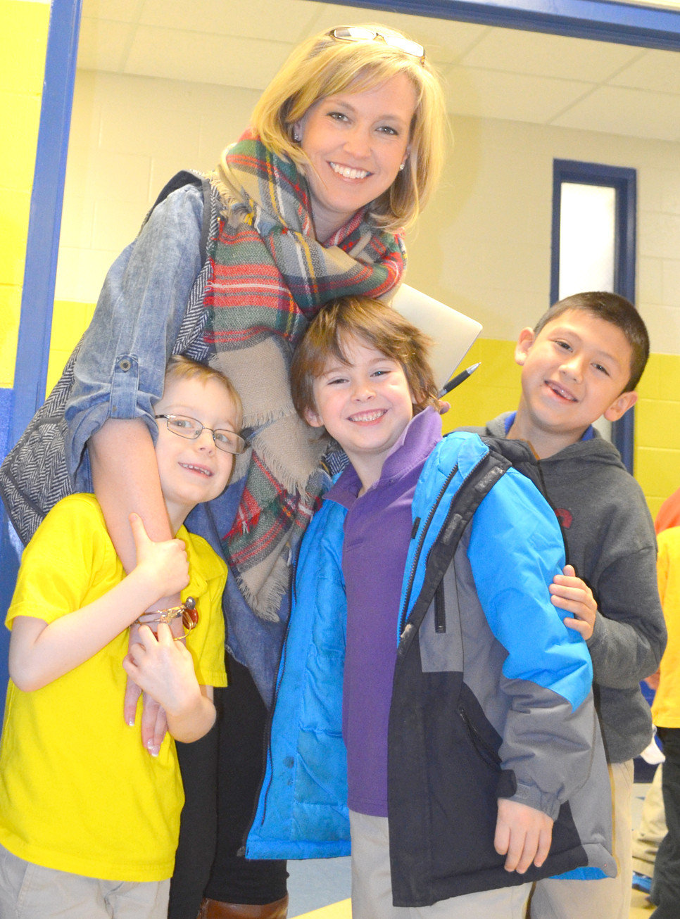MARTHA COLLINS, director of student achievement for Woodford County Public Schools, was stopped in the hallway for a group hug by Simmons Elementary students Jacob Durst, Parker Combs and Juan Marroquin, who are pictured left to right. (Photo by Bob Vlach)