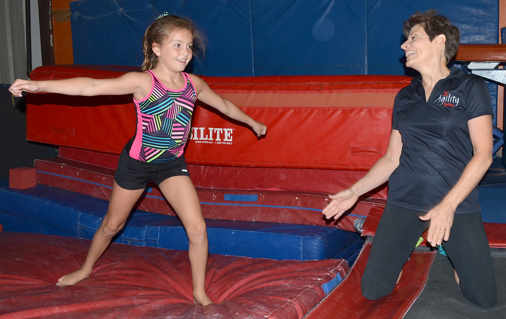 PEYTON WHITAKER and her coach, Kathy Huster, were all smiles during a recent training session at Agility Gymnastics Academy in Versailles. (Photo by Bob Vlach)