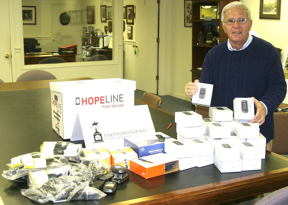 DON VIZI, executive director of the Woodford County Chamber of Commerce, with 50 or so cell phones donated to Verizon's HopeLine program, which gives new phones to victims of domestic abuse. The old phones are scrubbed, recycled or sold, and Verizon uses the proceeds for grants to non-profit groups and agencies around the country. (Photo by John McGary)