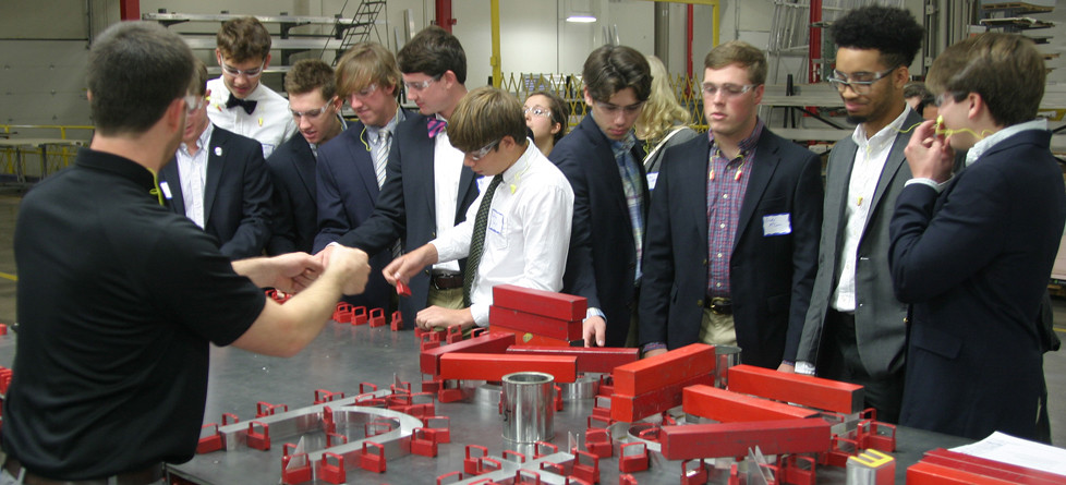 RUGGLES SIGN EMPLOYEE Todd Johnson shows a group of WCHS students the powerful magnets used in some of the company's signs. The magnets are used to keep letters in place until the adhesive dries. (Photo by John McGary)