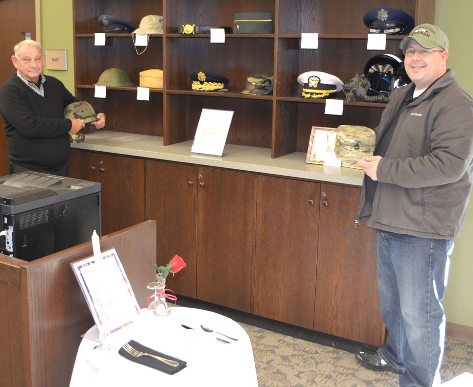 ARMY VETERANS Jim Shane, left, who served in Vietnam, and Jeremy Emerson, who served in Afghanistan, are pictured with a display of military hats, caps and helmets a