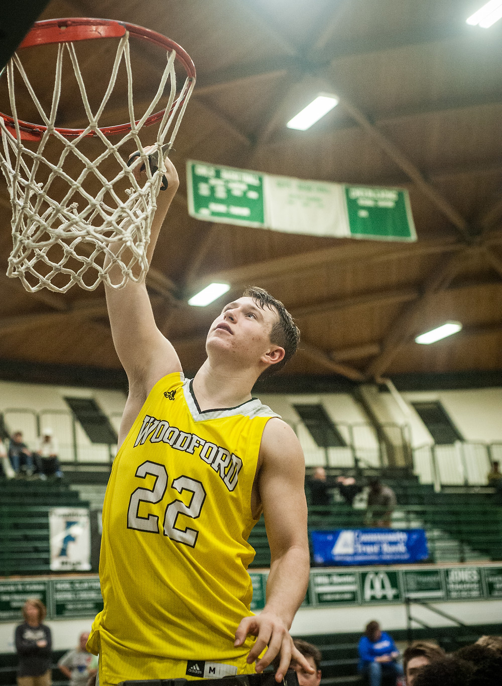 WCHS JUNIOR BEN NASH helps cut down the net after the Jackets' District championship win on Friday, Feb. 23 at Western Hills High School.  (Photo by Bill Caine)