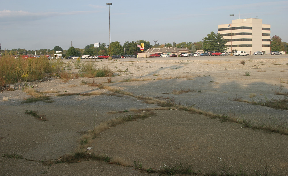 NO PROGRESS? The old Versailles Center today looks much like it did in September of 2014, when this photo was taken from the site where developers want to build a Holiday Inn Express and Suites. (File photo by John McGary)