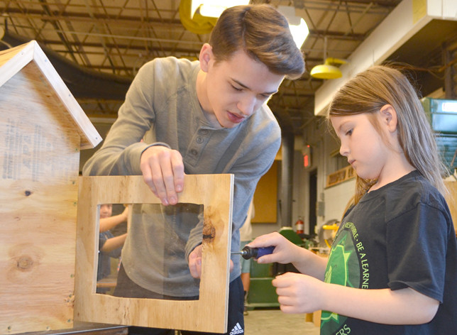 EVIE DUNCAN used a screwdriver to secure a clear plastic window onto the exterior door of a Little Free Library, with some guidance and help from Woodford County High School sophomore Jay Willis. (Photo by Bob Vlach)