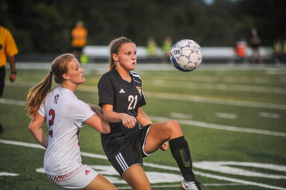 MACKENZIE TUCKER keeps her eye on the ball while battling for position with a Scott County defender in the Lady Jackets' Sept. 20 game. (Photo by Bill Caine)