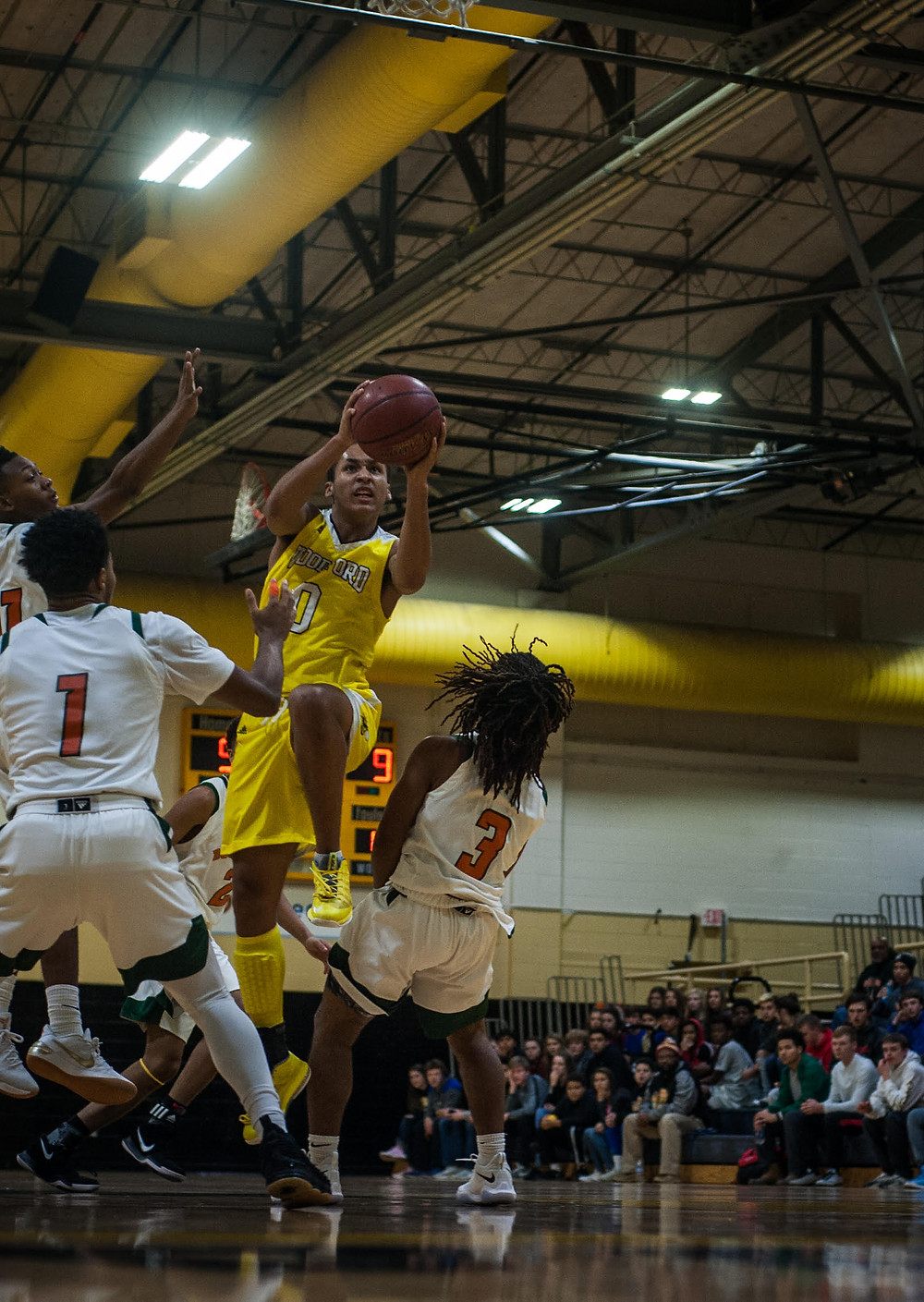 JUNIOR GUARD ANTHONY TABOR floats past a pair of Frederick Douglass High School defenders in the Jackets win on Dec. 20 in the Woodford County Invitational semi-final. (Photo by Bill Caine)