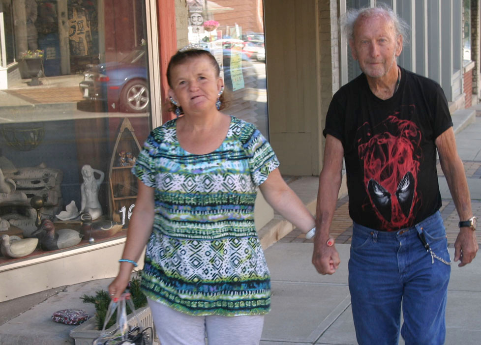 """JEANETTE AND ROBERT PHELPS take a daily stroll up South Main Street, but expect to be back on their bikes, or walking alongside them, soon. Asked why their marriage has lasted 16-plus years, she said, """"We're still together because he's good to me and I'm good to him and we need each other ."""" (Photo by John McGary)"""