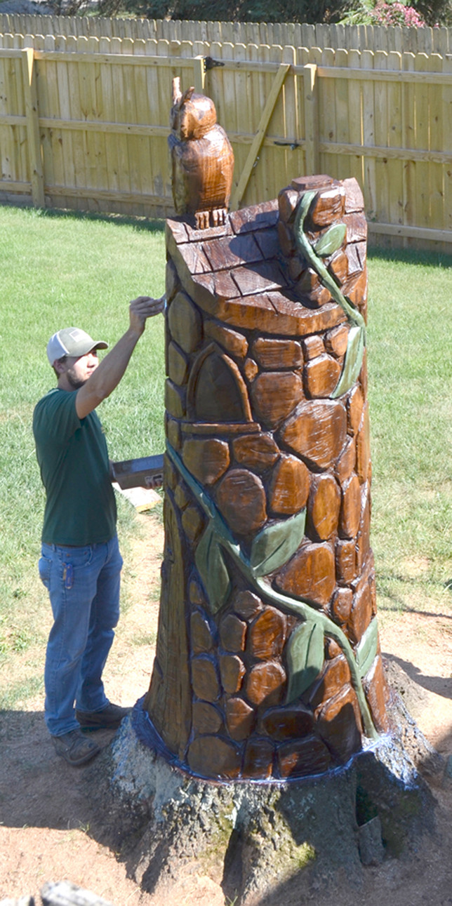 AN OWL SITS ATOP a fairytale sculpture carved out of a pin oak tree stump in Debora Nichols' backyard. Her nephew, Sam Sigmon, is pictured applying a coat of polyurethane to his chainsaw art. (Photo by Vlach)