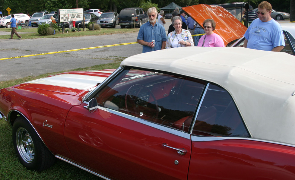 """A CAR CRUISE at Millville Hillbilly Daze attracted the likes of this '68 Camaro, owned by Barry Ginter, left. Admiring the redone sports car, which Ginter said he only drove on """"nice days,"""" are, from left, Ginter, Earleen Ginter, Jill Hartley and Michael Hartley. (Photo by John McGary)"""