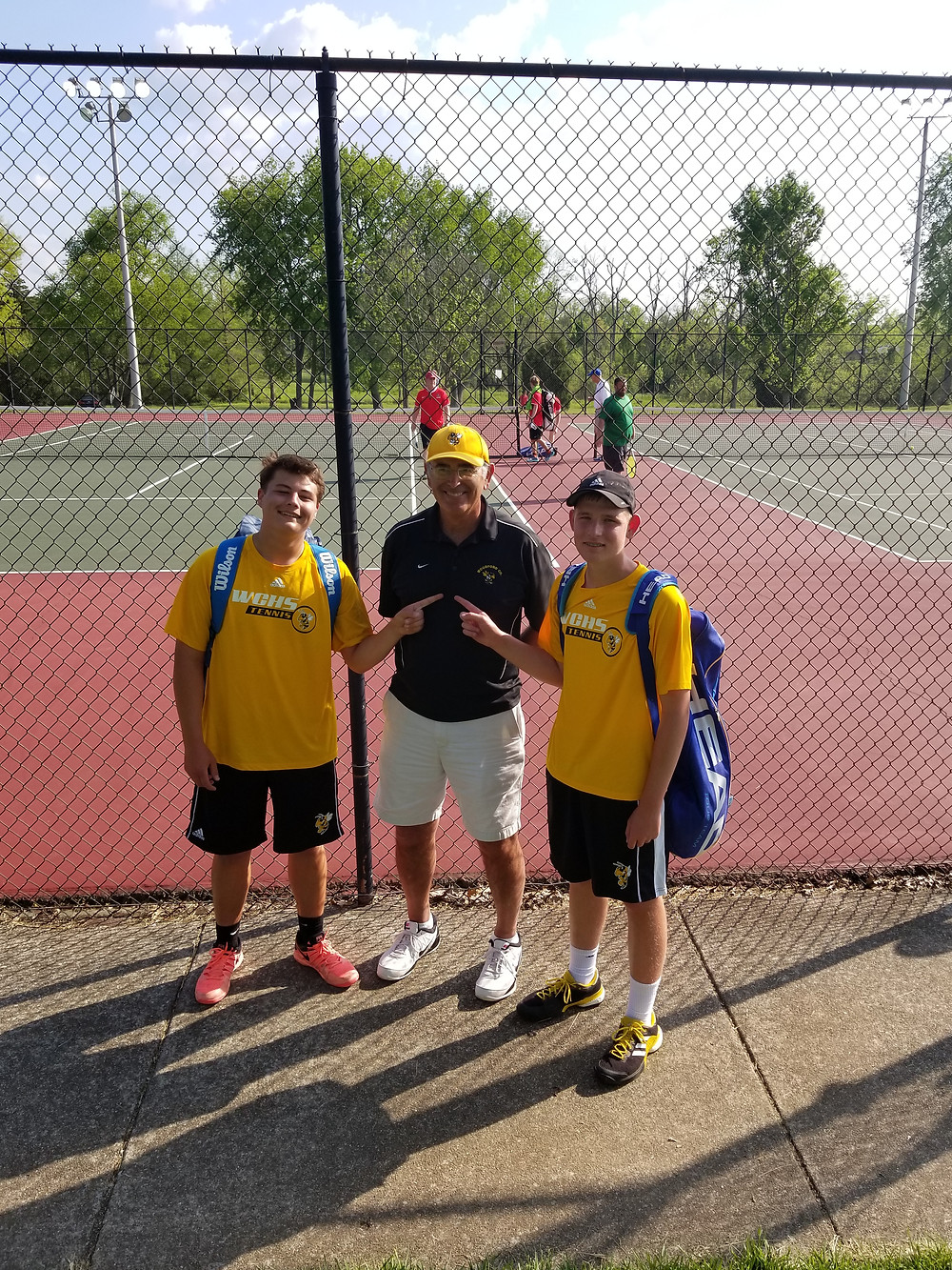 WCHS DOUBLES TEAMMATES, Mason McIntyre, left, and Evan Bentley, right, pose for a photo with Coach Stan Watts. The duo qualified for the state tennis tournament by reaching the regional semifinal. (Photo submitted)