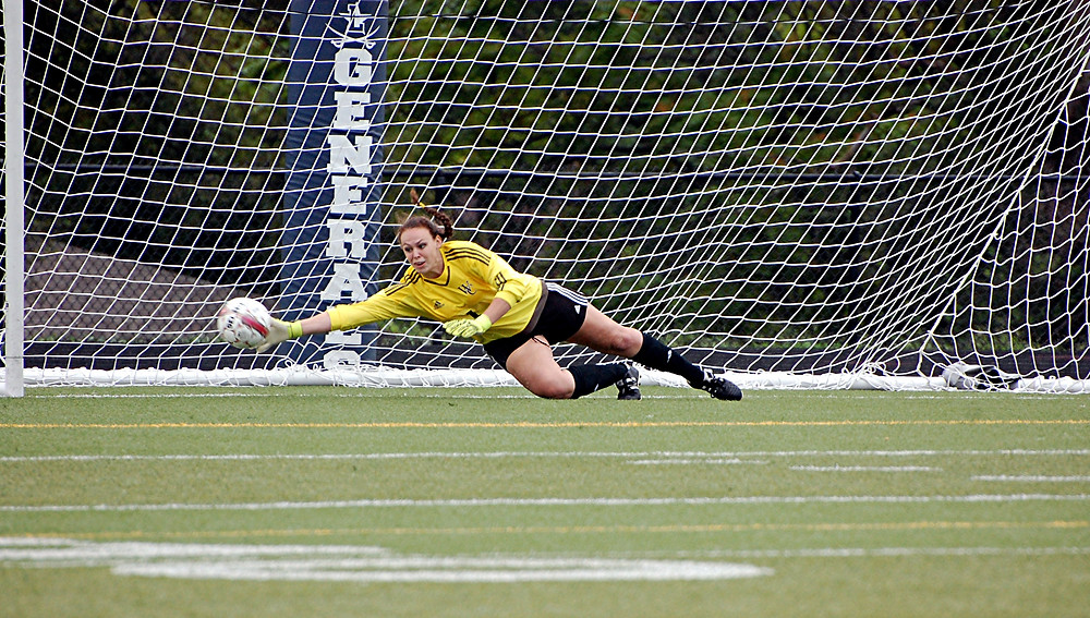 LEILA GRAF dives to stop a penalty kick in Woodford County High School girls' soccer game at Lafayette against Henry Clay on Saturday, Aug. 20, in the semifinals of the Fayette County Spectacular. Despite getting her hand on this ball, it got past the senior goalkeeper and into the lower left corner of the net. Henry Clay eventually won the game, 3-2, after 12 penalty kicks. (Photo by Rick Capone)