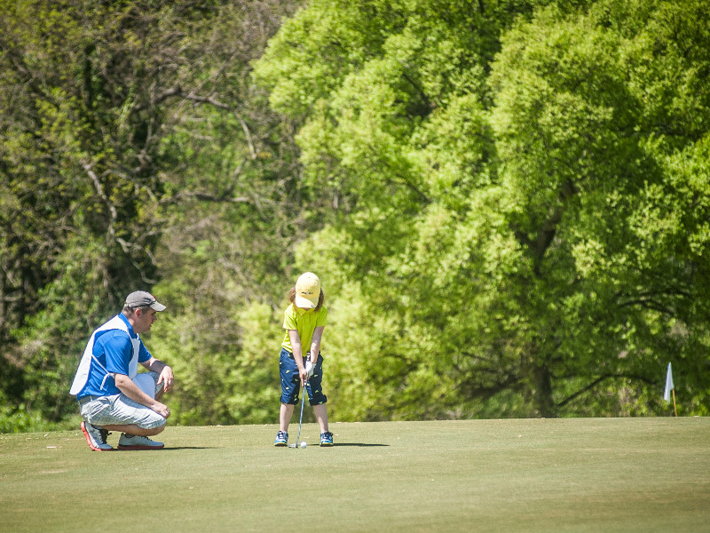 ABIGAIL CAINE, 7, carefully lines up a putt under the watchful eyes of her dad, Bill Caine. (Photo by Gretchen Caine)
