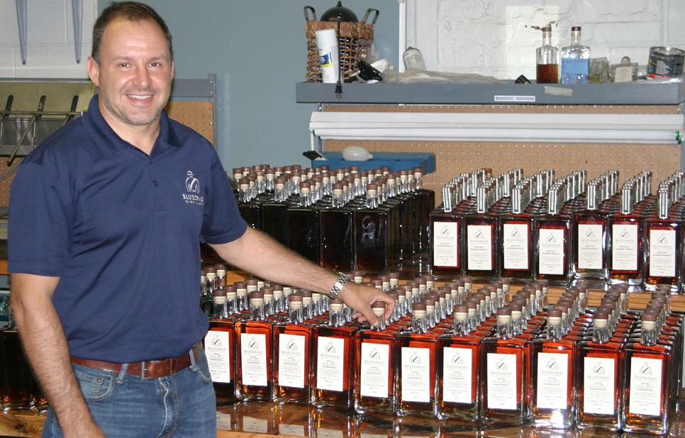 SAM ROCK, lawyer-turned bourbon maker, shows off some of Bluegrass Distillery's wares. The 1989 Woodford County High School graduate said his company should be in the black by the end of the year – with plans for expansion. (Photo by John McGary)