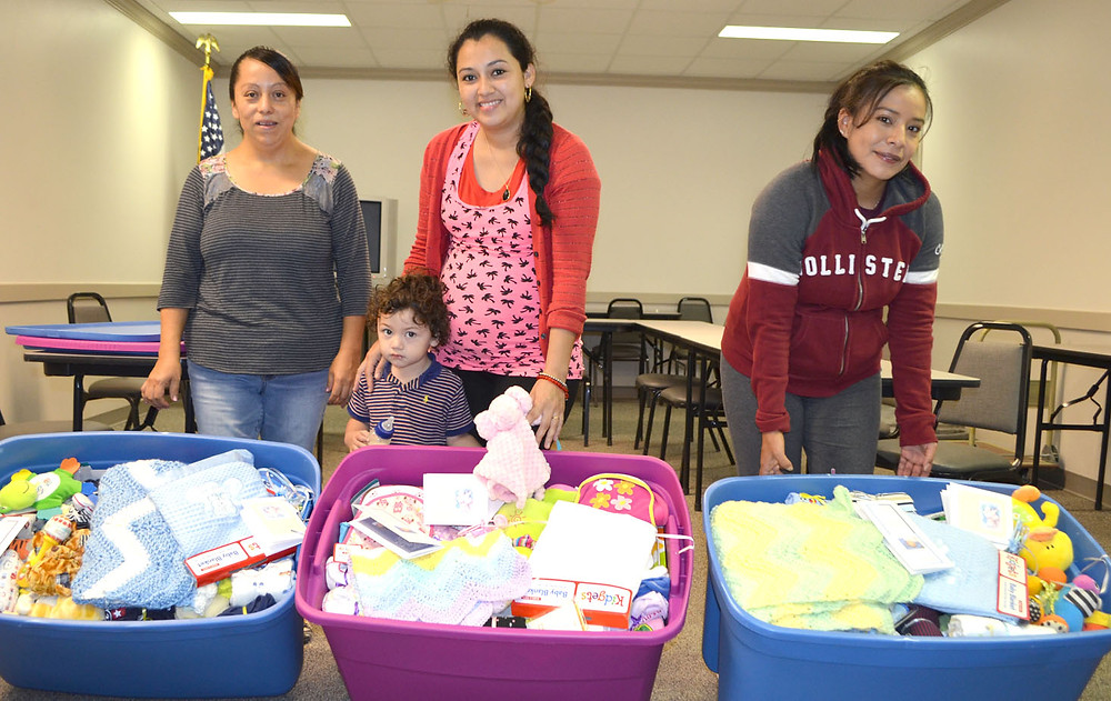 NEW AND EXPECTANT MOTHERS received Little Man's Legacy Totes during a very special birthday party at the Woodford County Health Department on Monday morning, Aug. 28. From left are Macaria Flores, with her two-year-old son, Esvin, Martha Nava and Adela Moreira. (Photo by Bob Vlach)