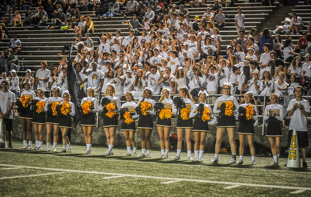 WOODFORD COUNTY cheerleaders patrol the sidelines Friday, Sept. 15, at Community Stadium. (Photo by Bill Caine)