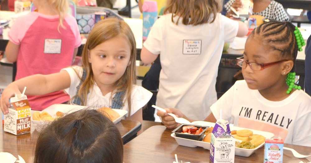 KINDERGARTNERS Hayden Barber, left, and Qua'leeah Gowdy ate lunch on the first day of school at Southside Elementary Aug. 8. An addition, which nearly doubled the size of the cafeteria and kitchen, was completed this summer. (Photo by Bob Vlach)