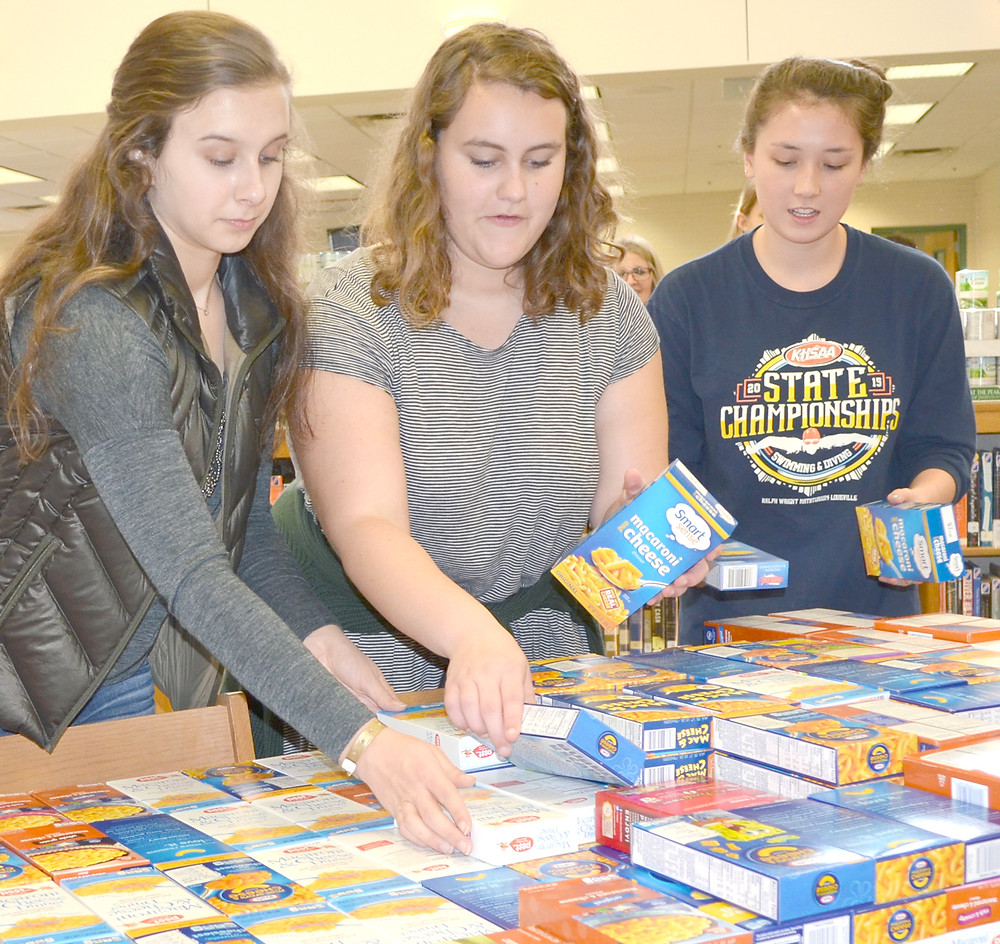 """OLIVIA BACK, Hinzee Smith and Maddie Gatewood, pictured left to right, sorted boxes of macaroni and cheese, donated during the Thanksgiving Food Drive at Woodford County High School. """"It just feels good to help people,"""" said Hinzee, a junior. (Photo by Bob Vlach)"""