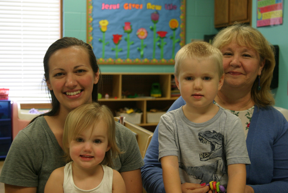 MEGAN CECIL, left, will be the teacher at Journey Church's first full-day pre-school class, which is open to four-year-olds. On her lap is her daughter, Ellie. On the lap of Journey pre-school director Joni Edester is Cecil's son, Raylan, who'll be one of the 12 students in the class. (Photo by John McGary)