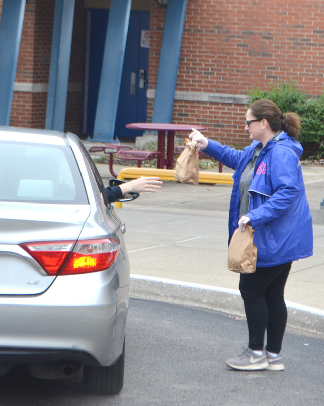 PRINCIPAL TIFFANY COOK took a lunch out to the car of a Simmons Elementary School family Monday. She said hi and encouraged a student inside the car to continue reading at home. Free lunches are being given to students at all public school sites in Woodford County this and next week in response to schools being closed because of the COVID-19 pandemic. (Photo by Bob Vlach)