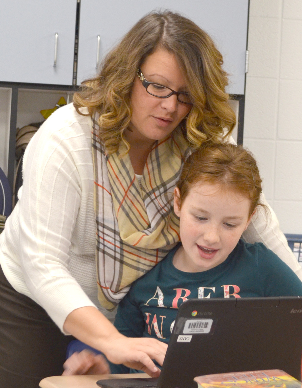 ANGELA BENTLEY, the Teacher of the Year at Huntertown Elementary School, offered some guidance to Cassidy Stiefel. The fourth-grader was using a computer tablet on a writing project. (Photo by Bob Vlach)