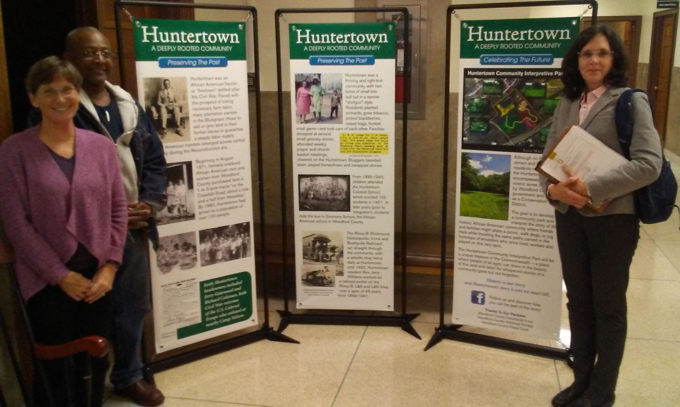 THE MOBILE HUNTERTOWN COMMUNITY displays were mounted outside the Fiscal Courtroom during Tuesday's court meeting. From left are Sioux Finney, Donald Morton and Magistrate Mary Ann Gill (Dist. 7). (Photo by John McGary)