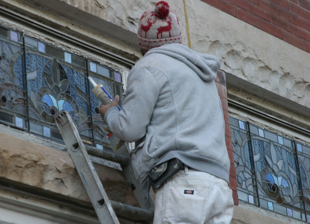 NEW CAULK was applied to an old stained-glass window at the Amsden Building, which was constructed in 1889 and purchased last March for $160,000 by three men who went to college together. By mid-December, a coffee shop, mercantile store and bourbon bar will be open there. (Photo by John McGary)