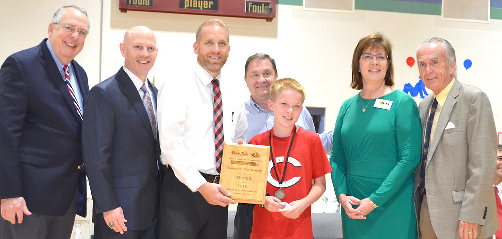 """SOUTHSIDE ELEMENTARY School fifth-grader Keegan Connell and Principal Jason McAllister accepted an award from the Kentucky School Boards Association (KSBA) for winning the inaugural """"Battle of the School Buildings"""" competition for energy efficiency. From left are KSBA Executive Director Mike Armstrong, Woodford County schools Superintendent Scott Hawkins, McAllister, Woodford County schools Energy Manager Ralph Slone, Keegan, KSBA Energy Services Coordinator Martha Casher and Woodford County Board of Education Chair Ambrose Wilson IV. Wilson, who represents Midway on the board, accepted an award given to Northside Elementary, which finished third in the """"Battle of the School Buildings"""" competition. (Photo by Bob Vlach)"""