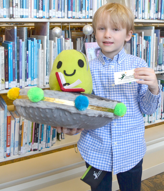"""JAN ROOZEN, 5, now has his very own Kindercard to check out books and other materials at the Woodford County Library. Kindergartners who sign up for this special library card by April 1 also receive a """"Bonkers for Books"""" headband and wallet. Bonkers is pictured at left. (Photo by Bob Vlach)"""