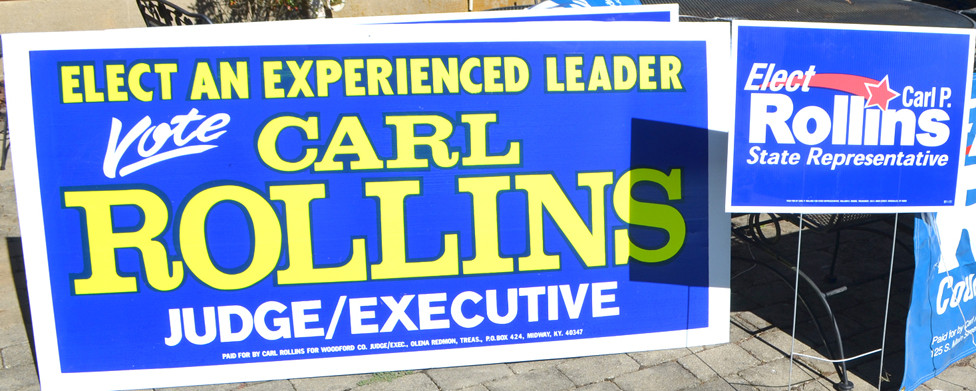 FORMER MIDWAY MAYOR Carl Rollins lost his only bid for public office when he ran for Woodford County judge-executive. He was elected and re-elected state representative. The difference in a yard sign – usually measuring 18-inches-by-24-inches – and a larger sign seen along busy roadways – typically 4-feet-by-8-feet – are obvious. (Photo by Bob Vlach)