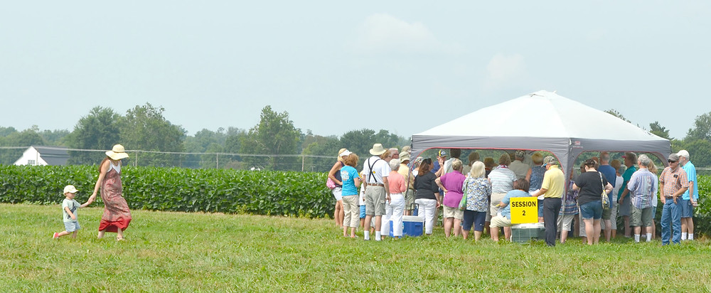 FOLKS GATHERED for an educational session on a soybean crop at Sycamore Farm during last year's Woodford County Farm Tour. A mother and child are also pictured on this 1,200-acre Shannon Run Road farm. (File photo by Bob Vlach)