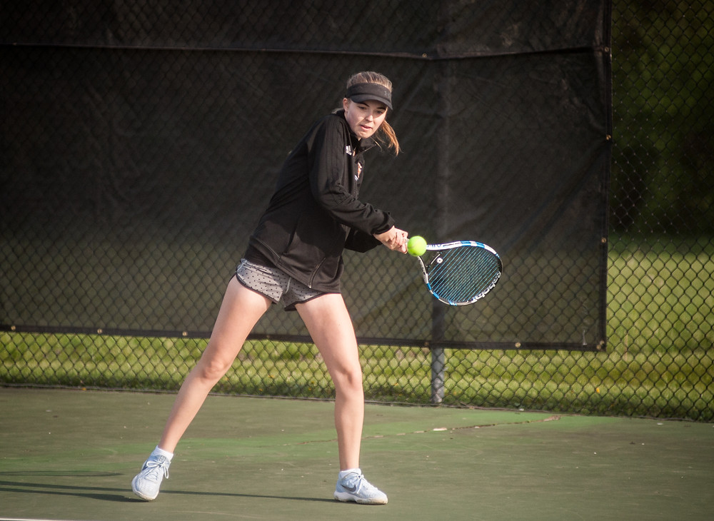 WCHS JUNIOR ADDISON BECK returns a serve at the Woodford County Invitational on Saturday, April 14. Beck was 2-0 on the day. (Photo by Bill Caine)