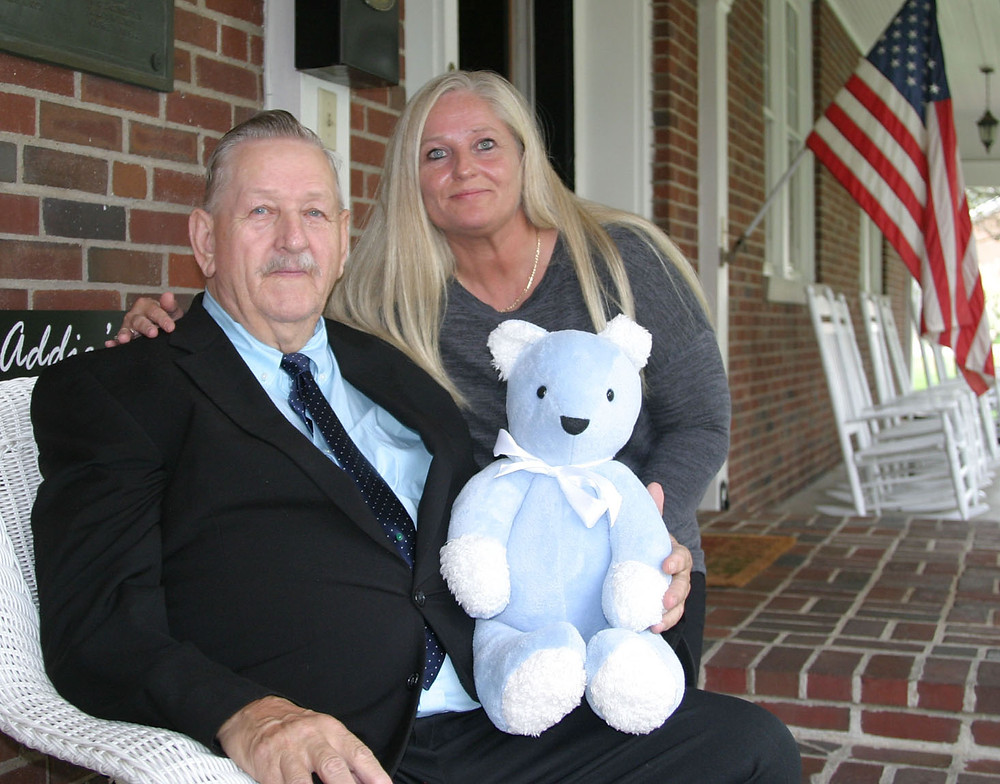 """AFTER WAYNE GIBSON lost his wife of 54 years, he couldn't sleep. Then hospice volunteer Shirley Bubany made a comfort bear and two pillows from her clothing, and Gibson began to sleep again. From left are Gibson, daughter Judy Powell, and Gibson's """"Momma Bear."""" (Photo by John McGary)"""