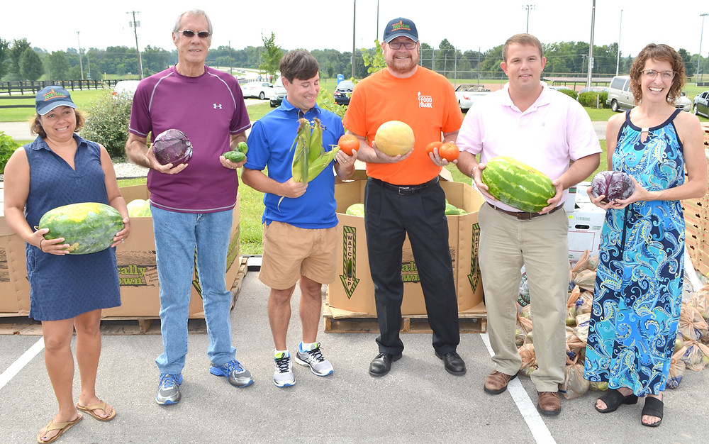 FRESH PRODUCE from the state's Farms to Food Banks program ensured local senior citizens received watermelons, cabbage, sweet corn and other Kentucky-grown vegetables on Tuesday morning. From left are Danielle Bozarth, program director for God's Pantry Food Bank in Lexington; Food Pantry for Woodford County volunteer Bill Phelps; state Rep. James Kay; Mike Halligan, CEO of God's Pantry; Versailles Mayor Brian Traugott; and Tamara Sandberg, executive director of the Kentucky Association of Food Banks, which supported legislation to fund the Farms to Food Banks program. (Photo by Bob Vlach)