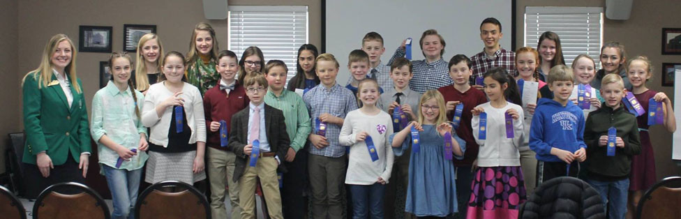 Participants in the 2019 Woodford County 4-H Communications Contest with their scoresheets and ribbons pose with 4-H State Secretary Delaney Simpson. Pictured, from front left, Delaney Simpson, Addie Patterson, Grace Pitchford, Bradford Lacefield, Braden Lacefield, Logan Rudd, Cooper Westfall, Audrey Franklin, Josiah Self, Kennedy Rudd, Manus Lavin, Sarah Vanzant, Emorey Metzger, Henry Smith, Caroline Gribble, Hunter Sutherland and Gabby Gampper; back, from left, Eliana Lee, Olivia Lee, Brianne Lacefield, Elizabeth Vanzant, Avery Franklin, Sawyer Gribble, Jacob Jones, Nicholas Vanzant, Cora Self and Gracie Metzger. (Photo submitted)