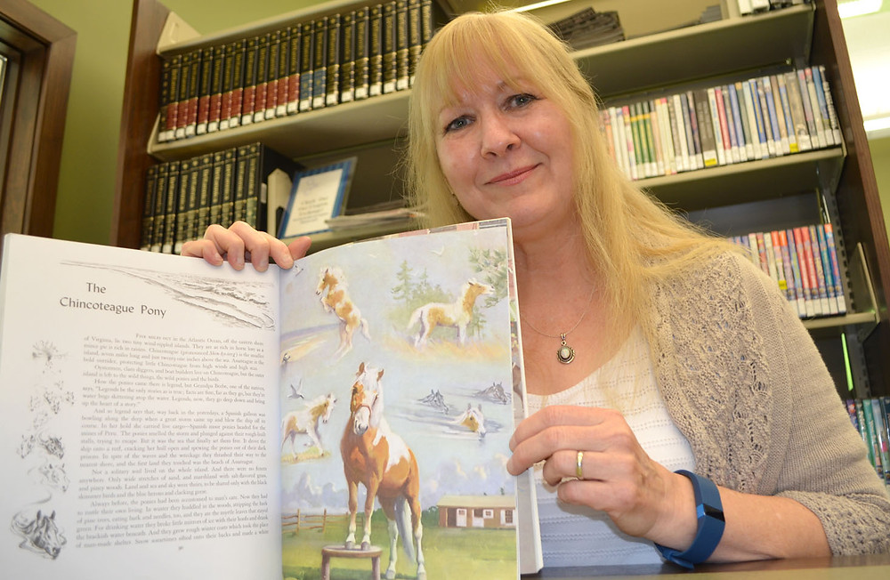 WRITTEN BY MARGUERITE HENRY and illustrated by Wesley Dennis, Album of Horses inspired Cindy Alvarado-Yeary to pursue a passion for art. She shares her love for creativity by teaching a variety of art classes at the Midway Branch Library. (Photo by Bob Vlach)
