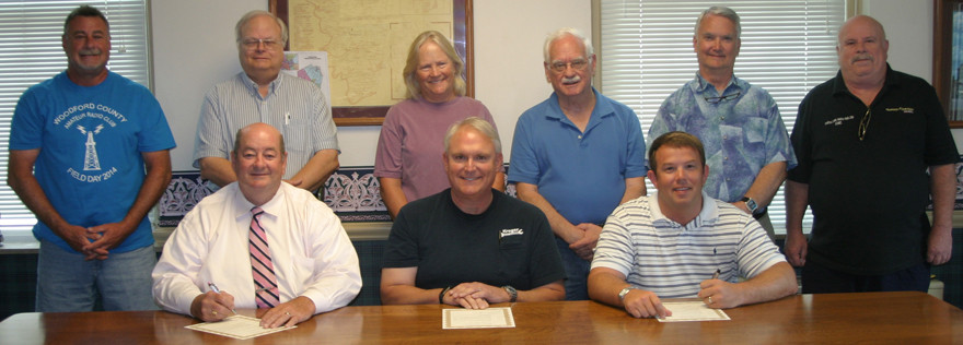 AMATEUR RADIO WEEK is June 19 to 24 in Woodford County, but members of the Woodford County Amateur Radio Club stay busy with training, projects and other ham-related matters year-round. From left, first row, are Woodford Judge-Executive John Coyle, club president Greg Shaw and Versailles Mayor Brian Traugott; second row, Todd Rose, Paul Harrington, Mary Shaw, Steve McFadden, Jerry Mueller and Ricky Nutter. (Photo by John McGary)
