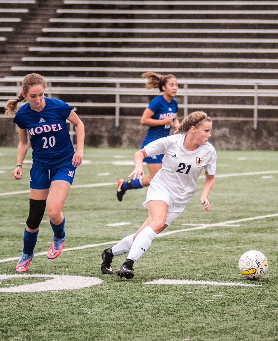MACKENZIE TUCKER moves past a Model defender in scrimmage play. (Photo by Bill Caine)