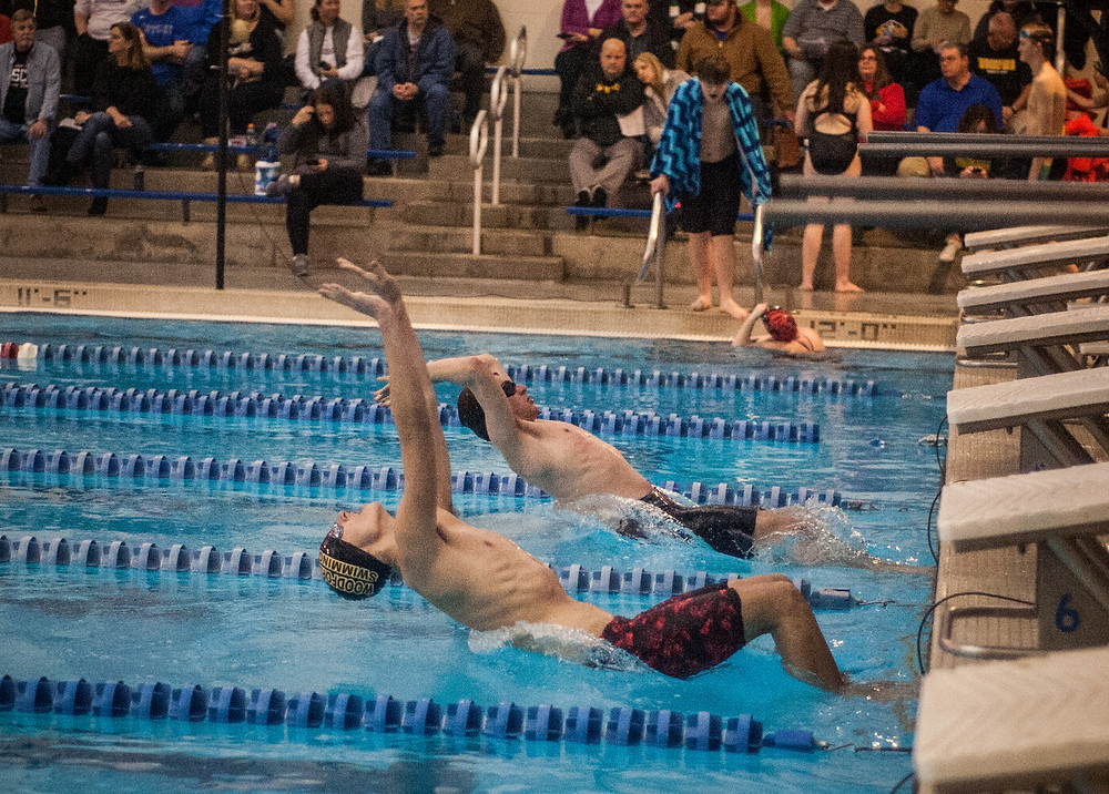 WCHS SOPHOMORE RILEY GARDNER,bottom, lunges to start the men's 100-yard backstroke at the meet with Scott Co. on Jan. 24. Gardner finished sixth in the event. (Photo by Bill Caine)