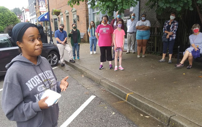 """MARLEY BUSH hadn't expected to speak to the more than 50 people taking part in Friday's march that visited the site of the racially-motivated burning of Midway's Second Christian Church on July 31, 1868.  """"I lived in this town all my life and my dad had to tell me that this happened (on) a street that I pass every day, (in) a town that I called home. I didn't know this happened to my people,"""" she said. (Photo by John McGary)"""