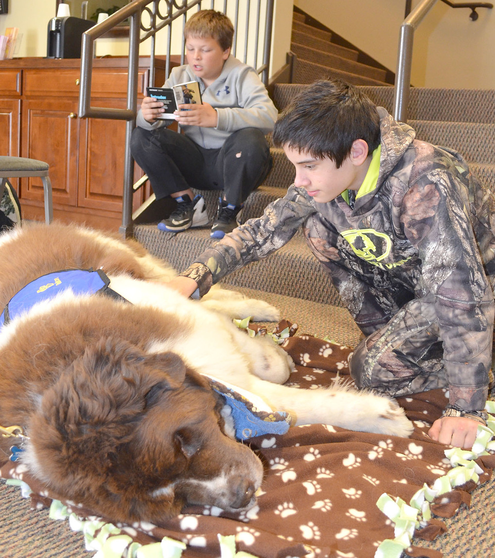 "BOURBON, a 6-year-old Newfoundland therapy dog, soaked in the attention of 13-year-old Logan Carter, while Juan Coronel, also 13, read him a story. ""He (Bourbon) loves children, and this breed's known for its sweet temperament,"" said Kathy Korona. She and Bourbon spent about an hour with middle school students in the Mentors & Meals program last Thursday afternoon, April 28. (Photo by Bob Vlach)"