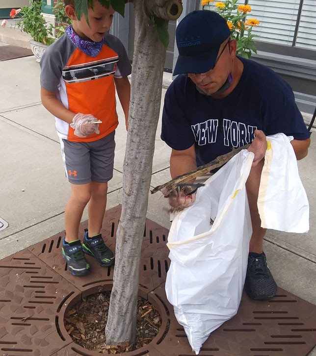 "JERRY GLANDER and his young son Ryker spent part of their Saturday morning picking up trash in downtown Versailles during the 7th annual Main Street Clean Sweep. Ryker said he'd found a battery, which, if not properly disposed of, would ""contaminate the soil and water."" (Photo by John McGary)"