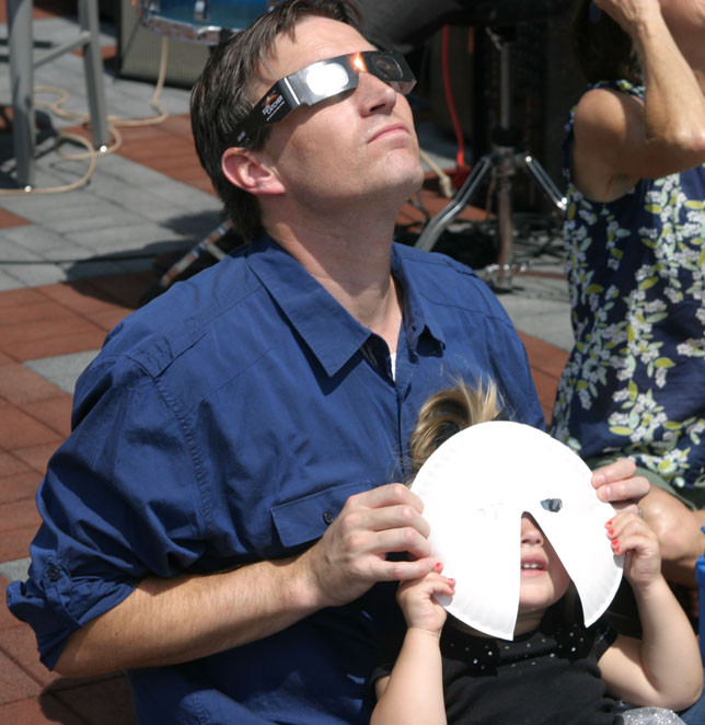 LANDON JONES of Nicholasville used a paper plate with eclipse lenses inside eyeholes to make it easier for his two-year-old son, Parker, to view the eclipse. (Photo by John McGary)